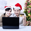 Christmas couple shopping online at home — Stockfoto