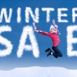 Woman jumping with a winter sale sign — Stock Photo