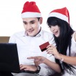 Young couple buying christmas gift online — Stock Photo