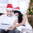 Christmas couple with digital tablet — Stock Photo #35513079