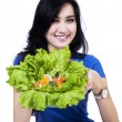 Attractive woman showing fresh salad — Stock Photo