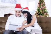Christmas couple with digital tablet — Stock Photo