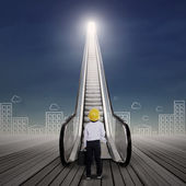 Businessman at escalator with cityscape — Stock Photo