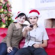 Happy christmas couple watching tv — Stock fotografie