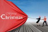 Asian businessteam pull christmas banner — Stock Photo