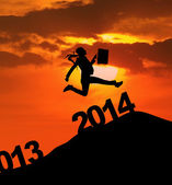 Businesswoman silhouette jumps over 2014 New Year — Stock Photo