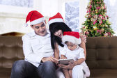 Christmas family play with a tablet — Stock Photo