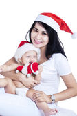 Happy mother and baby in red Christmas hats — Stock Photo