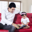 Stock Photo: Father and baby reading story book together