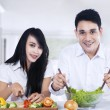 Happy couple preparing salad — Stock Photo