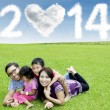 Happy family under cloud of new year 2014 — Stock Photo #36475867