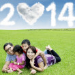 Happy family under cloud of new year 2014 — Stock Photo