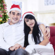 Smiling christmas couple in santa hats — Stock Photo