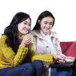 Two winter women using a laptop — Stock Photo