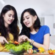Two women cooking vegetables salad — Stock Photo