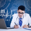 Young doctor working in front of laptop — Foto Stock