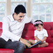 Stock Photo: Young father reading story book with his baby