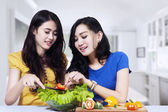 Asian women prepare salad together — Stok fotoğraf
