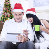 Christmas couple using digital tablet to shopping online — Stock Photo