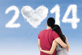 Couple looking at clouds shaped 2014 — Stock Photo