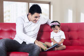 Father and baby reading story book together — Stock Photo