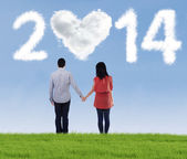 Happy couple holding hands looking in the future — Stock Photo