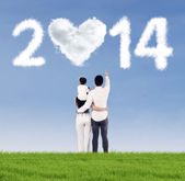 Happy family looking at the future of 2014 — Stockfoto