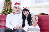 Smiling christmas couple in santa hats — Stock Photo