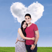 Smiling couple with clouds shaped of heart — Стоковое фото