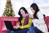 Two christmas woman using a laptop — Stock Photo