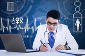 Young doctor working in front of laptop — Stock Photo