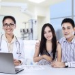 A female doctor with asian couple in doctor's office — Stock Photo