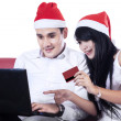 Happy couple buying christmas gift online — Stock Photo