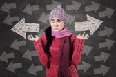 Winter girl looking at arrows — Stock Photo