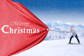 Young asian man is pulling christmas banner — Stock Photo