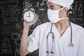 A doctor holding alarm clock — Stock Photo