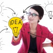 Business woman drawing light bulb — Stock Photo