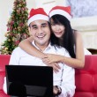 Couple in santa hats with a laptop — Stock Photo