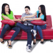 Stock Photo: Three people fighting for remote control