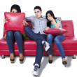 Three young people watching TV — Stock Photo