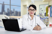 Female doctor writing prescription — Stock Photo