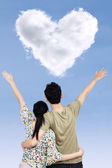 Happy couple with heart shape cloud — Stock Photo