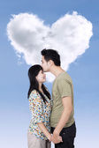 Romantic couple with heart shape cloud — Stock Photo