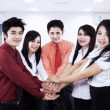 Business team joining their hands in the office — 图库照片
