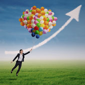 Businesswoman flying high with helium balloons — Stock Photo