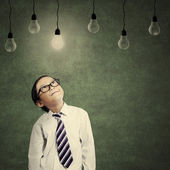 Cute little businessman looking at lit bulb — Stock Photo