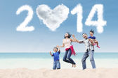 Happy family celebrate new year 2014 at beach — Stock Photo