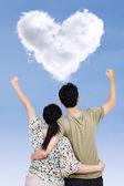 Success couple with heart shape cloud — Stock Photo