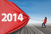 Woman pulling banner of new year 2014 — Stockfoto