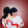 Boy hug mother holding love card on red — Stock Photo #39539395